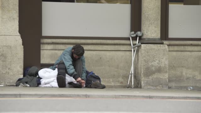 homeless man sitting on sidewalk in city - begging social issue stock videos & royalty-free footage