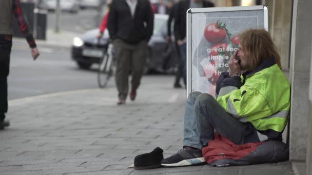 vidéos et rushes de homeless man sitting on sidewalk in city - avoir faim