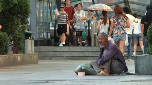 ws homeless man sitting on sidewalk / ningbo, zhejiang, china - begging social issue stock videos and b-roll footage