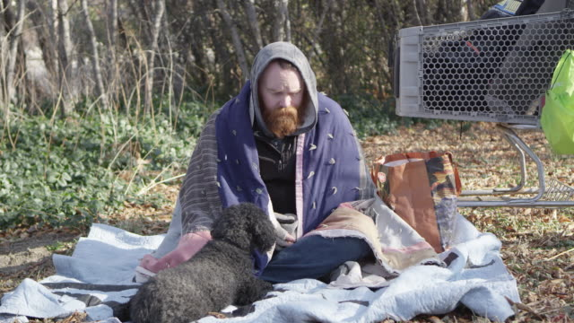 homeless man sitting on the ground petting dog - homelessness stock videos & royalty-free footage
