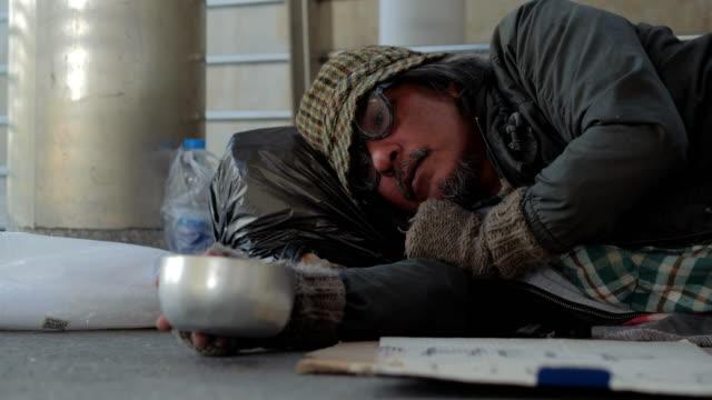 vídeos de stock, filmes e b-roll de sono do mendigo na rua, sem teto man dormindo no viaduto, voluntariado, dando - falência