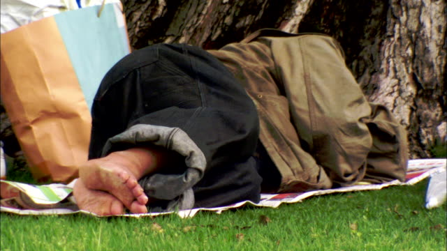 A homeless man sleeps in a park on a thin blanket, Japan. Available in HD.
