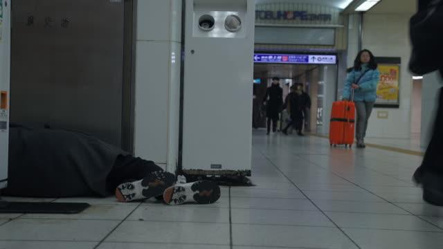 homeless man sleeps in subway station - tokyo, japan - homelessness stock videos & royalty-free footage