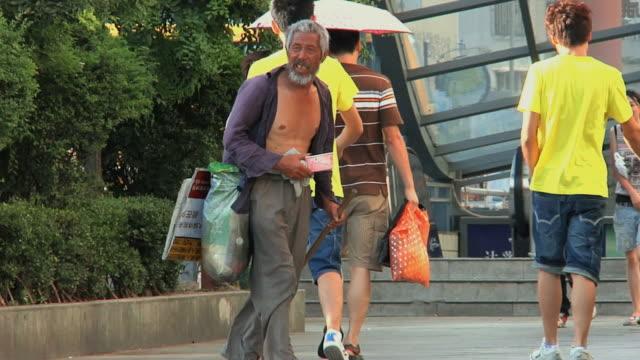 ms pan homeless man walking in pedestrian area / ningbo, zhejiang, china - beggar stock videos & royalty-free footage
