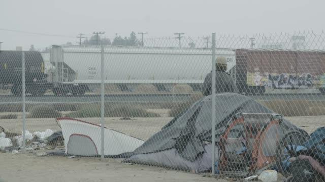 vídeos y material grabado en eventos de stock de homeless man watches train ride by, wide shot - terrenos a construir
