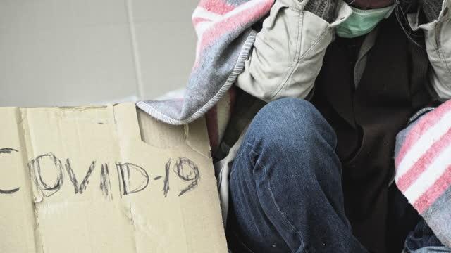 """vídeos de stock, filmes e b-roll de sem-teto com uma máscara médica sentado na rua perto da parede de tijolos e pedindo ajuda para """"covid-19"""". - pobreza questão social"""