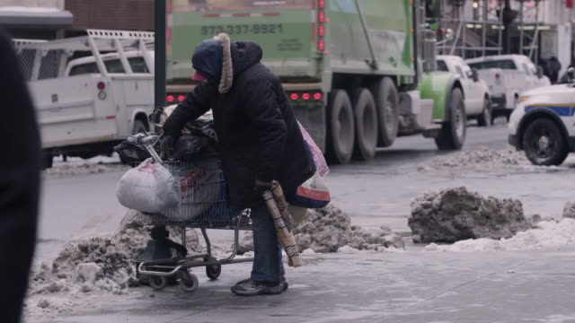 a homeless man with a shopping cart on a snowy day in new york city. - hemlöshet bildbanksvideor och videomaterial från bakom kulisserna
