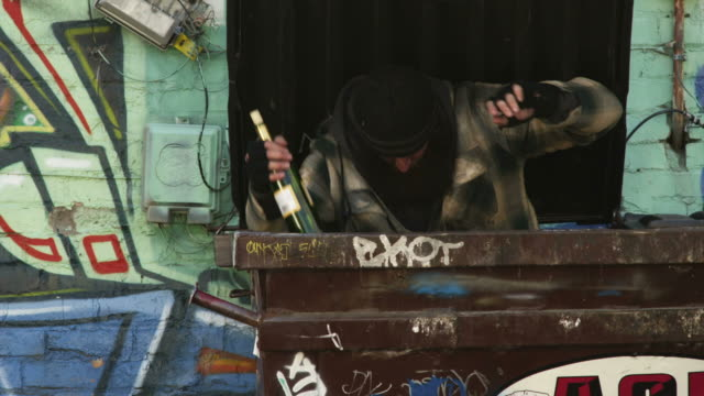 stockvideo's en b-roll-footage met ms homeless man with wine bottle exiting garbage container, salt lake city, utah, usa - afvalcontainer container