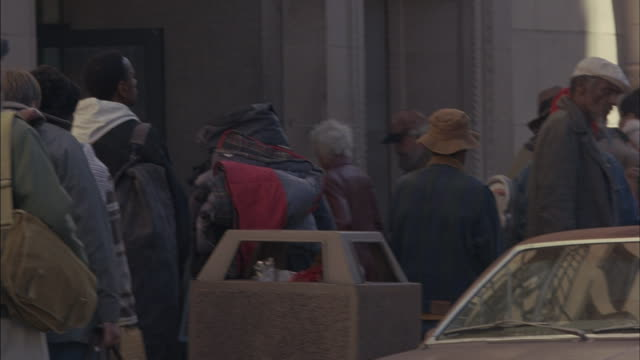 homeless men and women wait in line at a shelter. - unemployment stock videos and b-roll footage