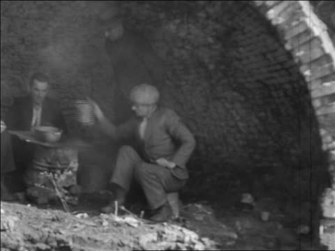 b/w 1935 3 homeless men sitting in abandoned coke oven cooking / pennsylvania / newsreel - 1935 stock videos & royalty-free footage