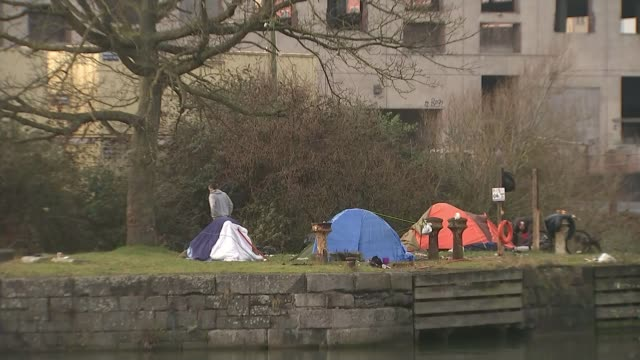 homeless numbers in uk could rise to over half a million by 2041; t25011713 / tx bristol: wide shot empty concrete building tents occupied by... - channel 4 news stock videos & royalty-free footage