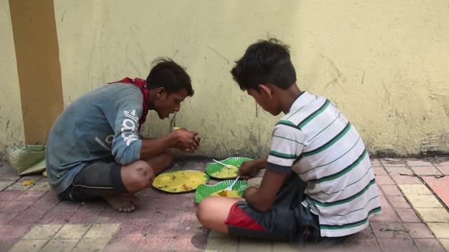 homeless people eat on footpath after volunteer distribute food during lockdown due to covid-19 coronavirus pandemic, on may 22, 2021 in guwahati,... - eating stock videos & royalty-free footage