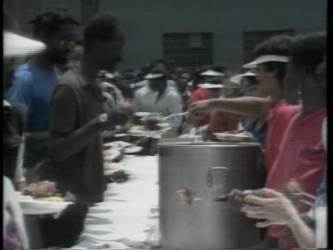 Homeless people line up on Skid Row to receive meals on May 25 1985 in Los Angeles California