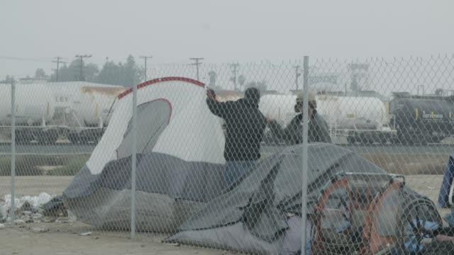 vídeos y material grabado en eventos de stock de homeless people move tent in lot, slow motion - terrenos a construir