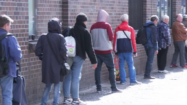 homeless people stand in a line to get food packages from the berliner stadtmission charitable organization on april 9 2020 in berlin germany the... - wohnungsprobleme stock-videos und b-roll-filmmaterial