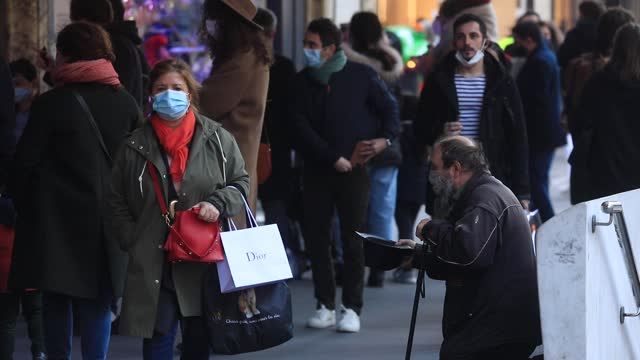 homeless person asks for money to people walking in department store district on november 28, 2020 in paris, france. after almost four weeks of... - exclusive stock videos & royalty-free footage