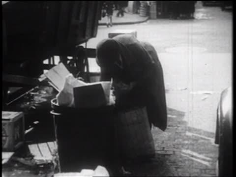 b/w 1939 homeless person digging thru trash can on city sidewalk / nyc / documentary - 放浪者点の映像素材/bロール