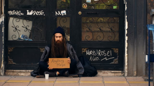 homeless person holding 'anything helps' cardboard and begging on crowded street - begging social issue stock videos and b-roll footage