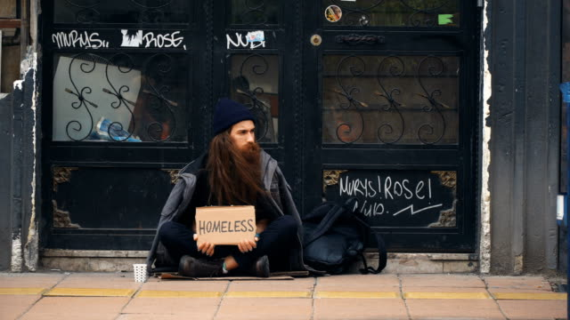 homeless person holding 'homeless' cardboard and begging on crowded street - homeless shelter stock videos & royalty-free footage