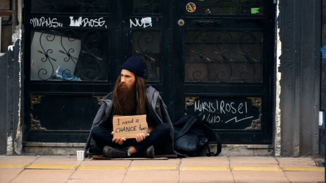 homeless person holding 'i need a chance' cardboard and begging on crowded street - charity benefit stock videos & royalty-free footage