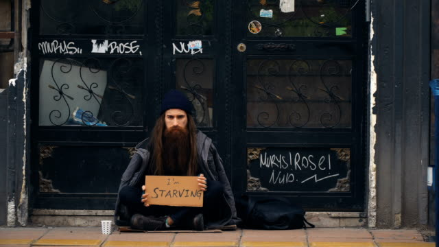 homeless person holding 'i'm starving' cardboard and begging on crowded street - beggar stock videos & royalty-free footage