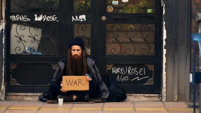homeless person holding 'war' cardboard and begging on crowded street - unemployment stock videos and b-roll footage