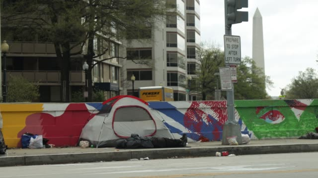 vidéos et rushes de homeless person lies on a sidewalk next to a tent april 1, 2020 at foggy bottom in washington, dc. the district of columbia has joined other states... - maryland état
