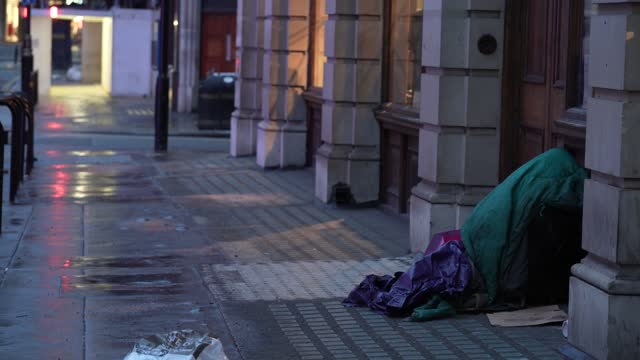 homeless person shelters under a shop window in winter conditions in london on february 8, 2021 in london, england - homeless shelter stock videos & royalty-free footage
