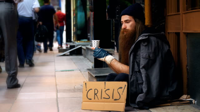 homeless person with 'crisis' cardboard and begging on crowded street - pleading stock videos & royalty-free footage