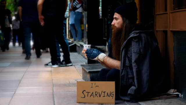 homeless person with 'i'm starving' cardboard and begging on crowded street - hungry stock videos & royalty-free footage