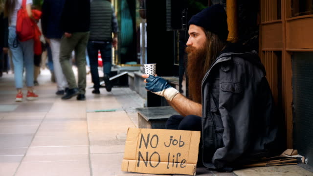 vídeos de stock e filmes b-roll de homeless person with 'no job no life' cardboard and begging on crowded street - desemprego