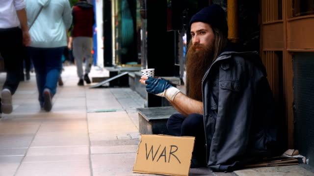 obdachlose mit ' war ' pappe und beging auf crowded street - war stock-videos und b-roll-filmmaterial