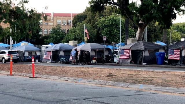 homeless veterans in westwood are encamped in tents draped with the american flag. - westwood neighborhood los angeles bildbanksvideor och videomaterial från bakom kulisserna