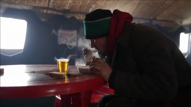 homeless warm themselves by a fire and are given a hot drink and food in temporary shelter in kiev set up by the government to help fight the cold... - homeless shelter stock videos and b-roll footage