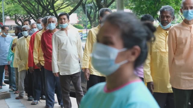 homeless wearing protective masks on their faces celebrate the muslim religious holiday of eid al-fitr as restrictions from the coronavirus pandemic... - kuala lumpur stock-videos und b-roll-filmmaterial