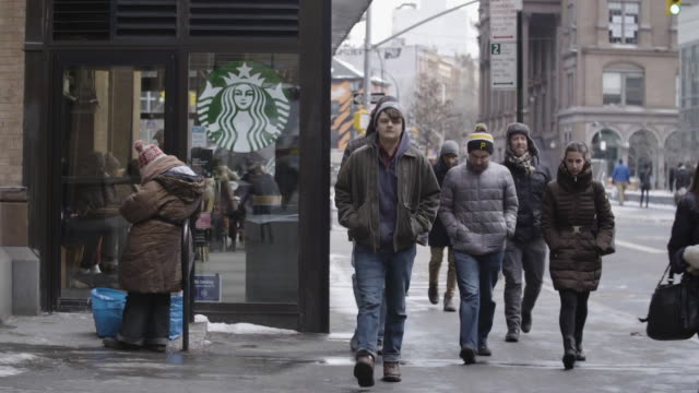 vídeos de stock, filmes e b-roll de homeless woman eats outside of starbucks as pedestrians walk by - starbucks