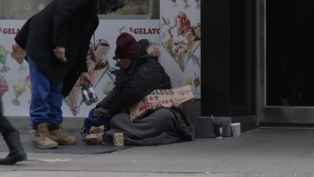 """homeless woman holding a """"homeless not hopeless"""" sign, sits on the sidewalk in front of a fast food restaurant and smiles as pedestrians walk by. a... - 放浪者点の映像素材/bロール"""
