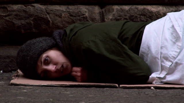 Homeless woman lying on street looking in distress