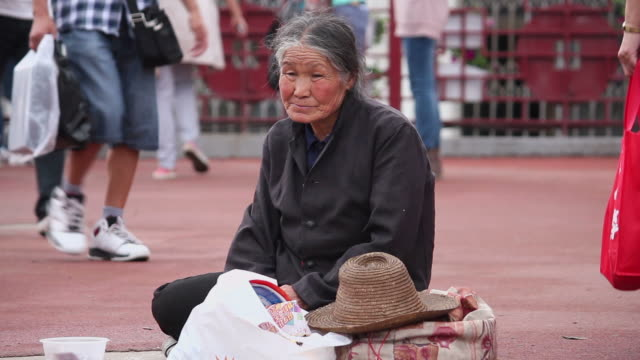 ws homeless woman sitting on sidewalk/xian,shaanxi,china - homelessness stock videos and b-roll footage