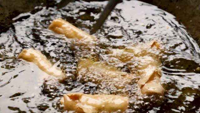 vídeos de stock, filmes e b-roll de homemade authentic fried asian spring rolls frying, cooking and stirred in hot boiling oil with metal tongs, static close up - crocante
