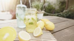 Homemade fresh lemonade with mint and ice. Making two lemon cocktail, lifestyle. Outdoor shot in summertime.