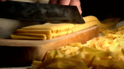 homemade fresh pasta: cutting pasta with a traditional knife on a wooden table