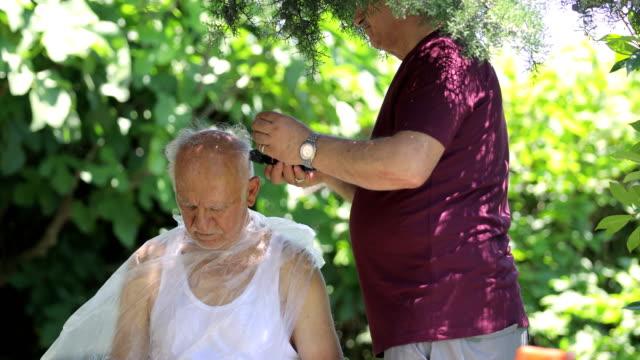 vídeos de stock, filmes e b-roll de diy cara de cabelo caseirocut durante covid-19, cortes de cabelo ao ar livre para evitar limpeza, corte de cabelo em casa sênior, filho cortou o cabelo de seu pai no jardim durante coronavirus covid-19 - salão de beleza