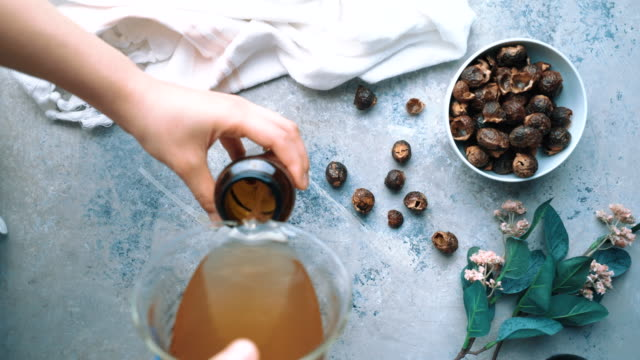 vidéos et rushes de savon liquide biologique fait maison, détergent fabriqué à partir de noix de savon (soapberry) - lessive produit d'entretien