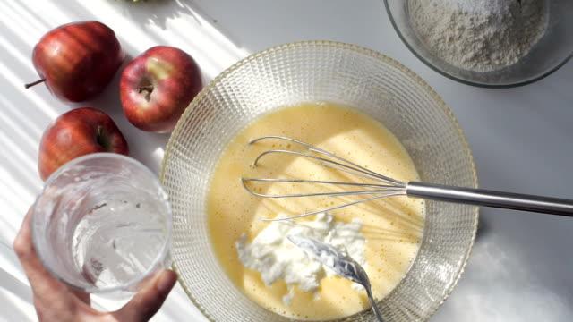 vídeos y material grabado en eventos de stock de pastelería casera. mujer añadiendo yogur y mezclando ingredientes para pasteles - rebozado
