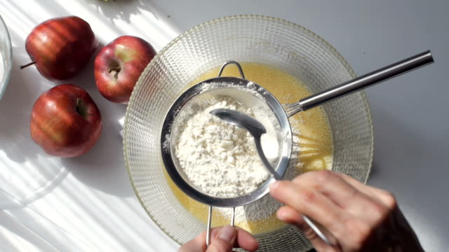 homemade pastry. young woman adds flour and mixes cake ingredients - batter stock videos & royalty-free footage