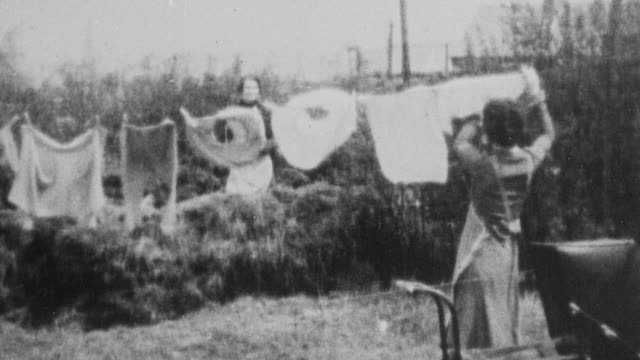 montage homemaker hanging laundry on a line in her yard while caring for her baby in a buggy by her side / united kingdom - homemaker stock videos and b-roll footage