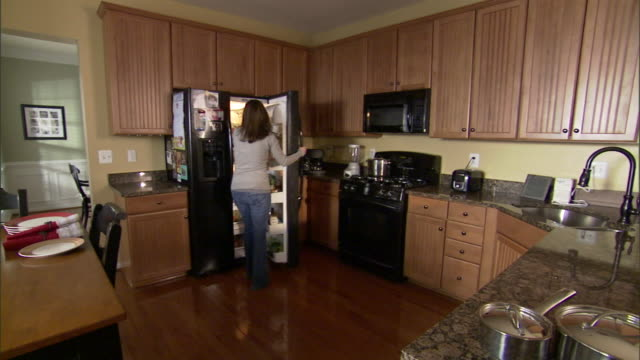 a homemaker removes a beverage from a refrigerator and walks to a sink. - toaster appliance stock videos & royalty-free footage