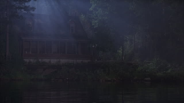 A homeowner enters his lakeside cabin on a foggy night.
