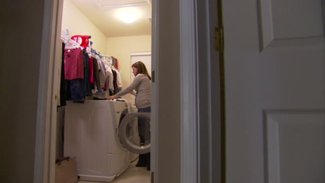 a homeowner hangs up clean clothes in her laundry room. - tumble dryer stock videos & royalty-free footage